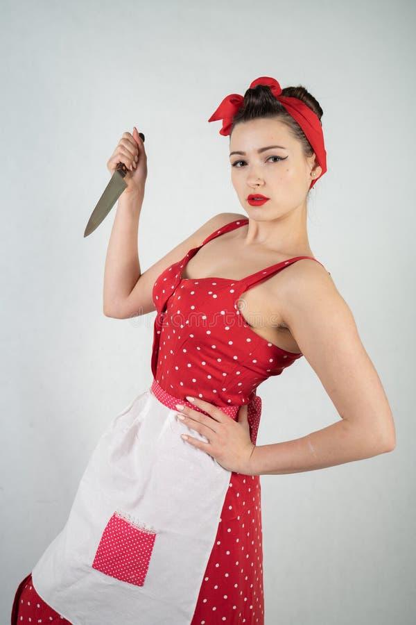 女孩主妇的危险别针红色葡萄酒圆点礼服的在她的手上站立与一把巨大的厨刀和愤怒高兴 免版税库存图片