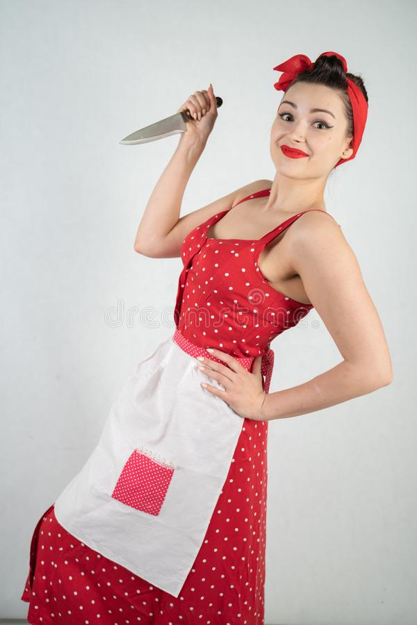 女孩主妇的危险别针红色葡萄酒圆点礼服的在她的手上站立与一把巨大的厨刀和愤怒高兴 免版税图库摄影