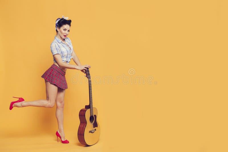 女孩举她的基于吉他的脚站立在黄色 免版税库存照片