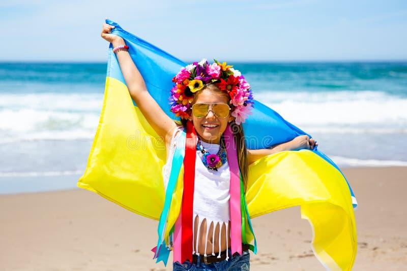 女孩举着振翼在天空蔚蓝和海背景的乌克兰的蓝色和黄旗 库存照片
