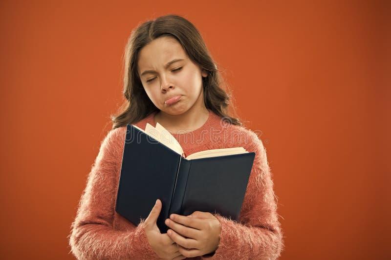女孩举行书读了在橙色背景的故事 孩子享用看书 书店概念 美妙的自由的孩子的 库存图片