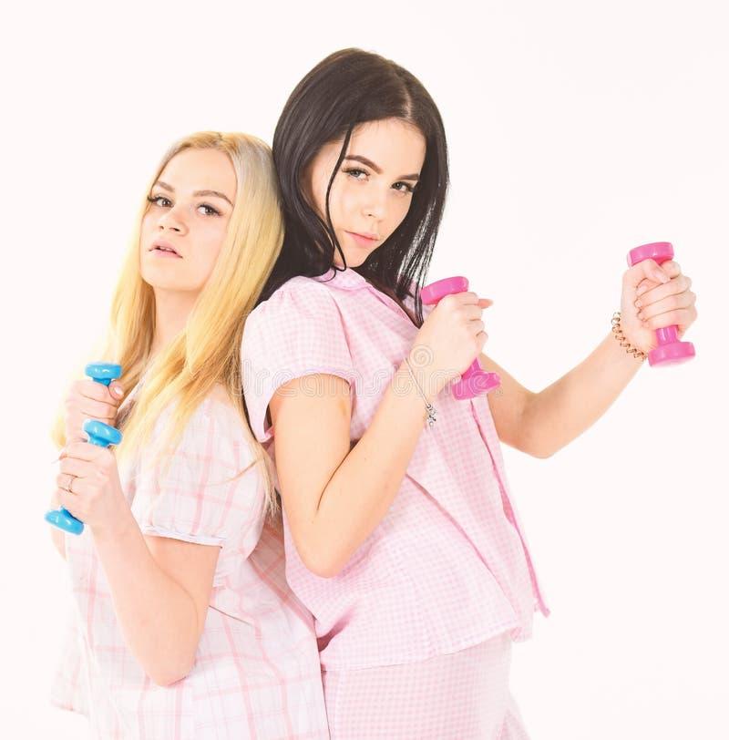 姐妹或最好的朋友睡衣的做体育 早晨运动概念 白肤金发和深色在严肃的面孔关心 免版税库存图片