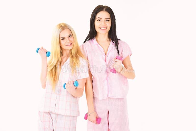 女孩举行哑铃,隔绝在白色背景 姐妹或最好的朋友睡衣的炫耀 早晨执行 库存图片