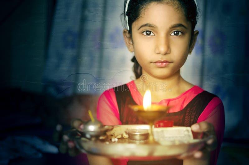女孩举行祷告板材欢迎的儿童画象 库存照片