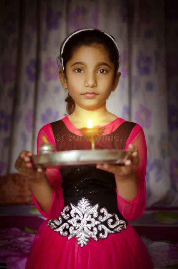 女孩举行祷告板材欢迎的儿童画象 免版税库存图片