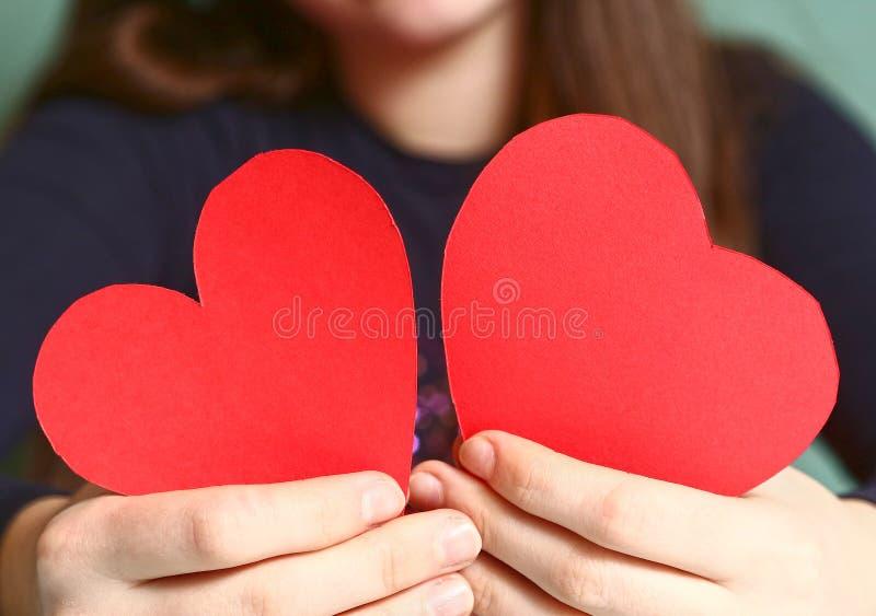 女孩举行红色纸两华伦泰心脏 免版税图库摄影