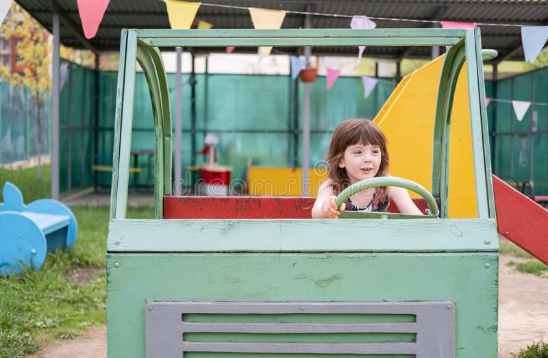 女孩乐趣刻画一辆木汽车的司机的在操场的五年 图库摄影