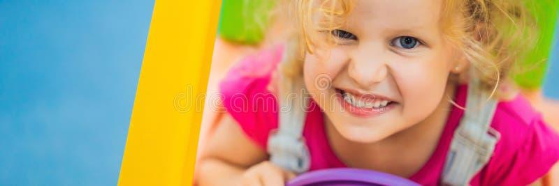 女孩乘坐玩具五颜六色的汽车横幅,长的格式 图库摄影