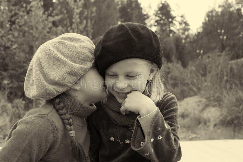 女孩互相告诉秘密,坐在公共汽车站 图库摄影