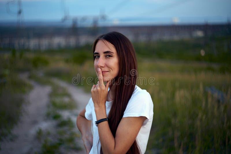 女孩产生了一个狡猾想法 注视狡猾 在嘴唇的手指 免版税图库摄影