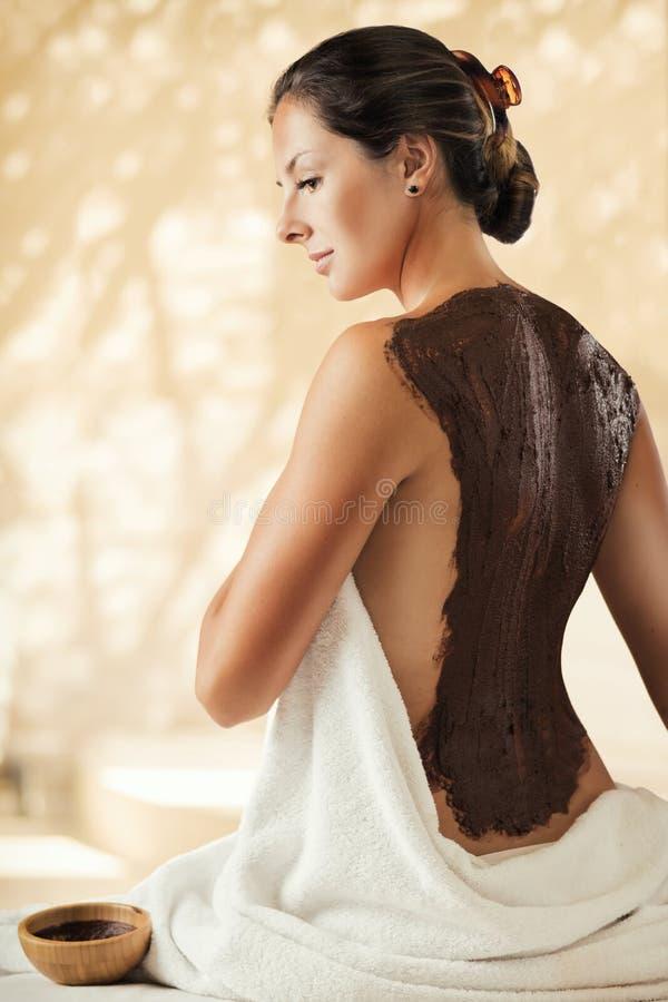女孩享受巧克力在温泉沙龙的身体面具 免版税库存照片