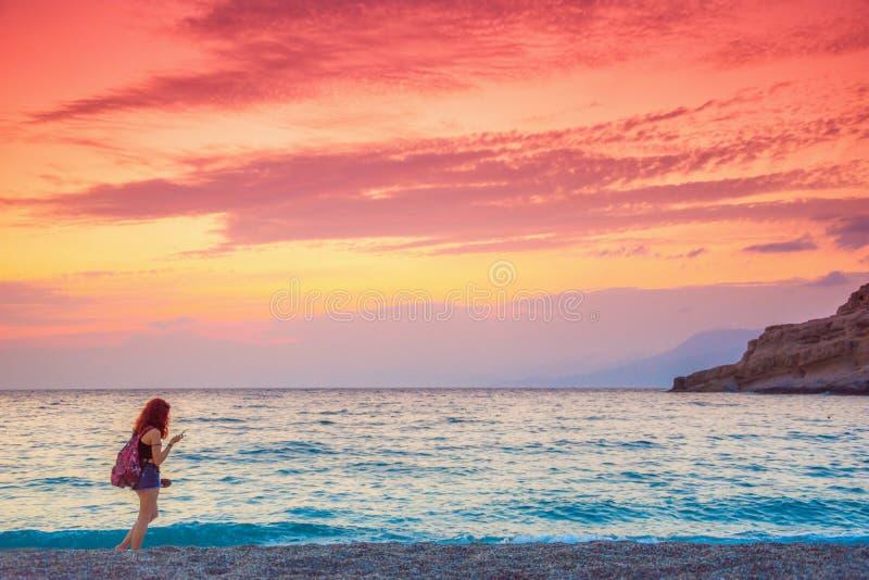女孩享受惊人的日落在Matala海滩  免版税库存照片