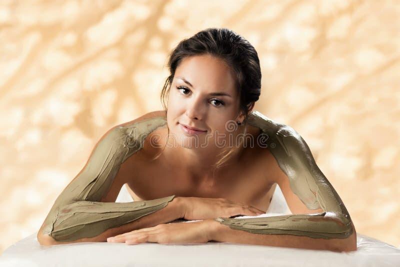 女孩享受泥在温泉沙龙的身体面具 免版税库存照片