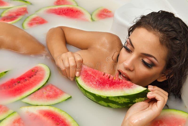 女孩享受浴用牛奶和西瓜。 图库摄影