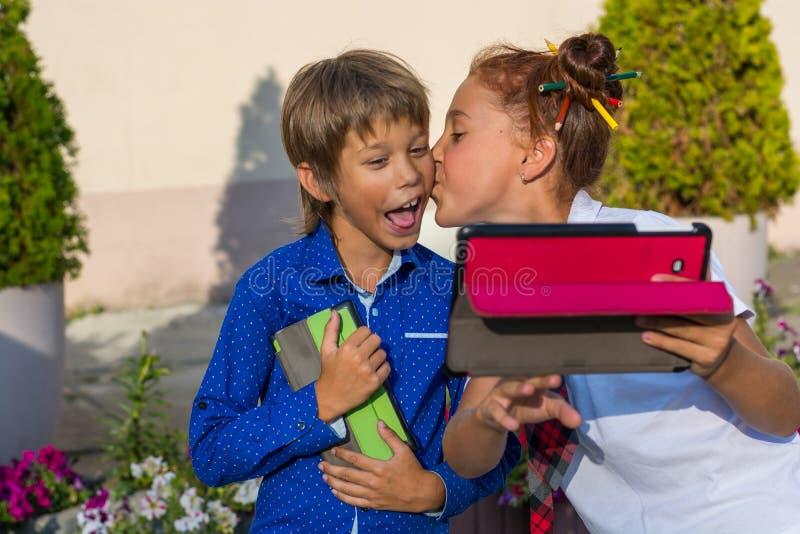 女孩亲吻她的弟弟并且做selfie 免版税库存照片