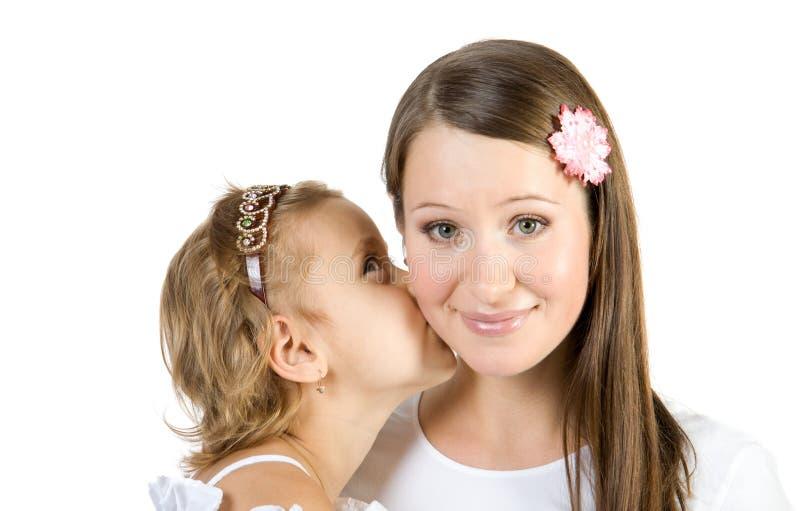 女孩亲吻小母亲 免版税图库摄影
