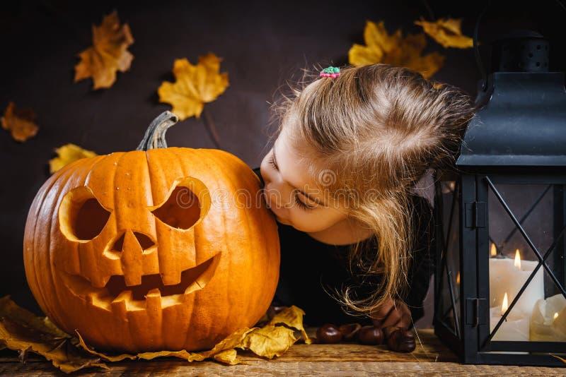 女孩亲吻一个万圣夜南瓜 免版税库存图片