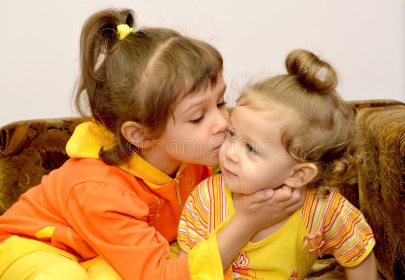 女孩亲吻更加年轻的妹 画象 免版税库存照片