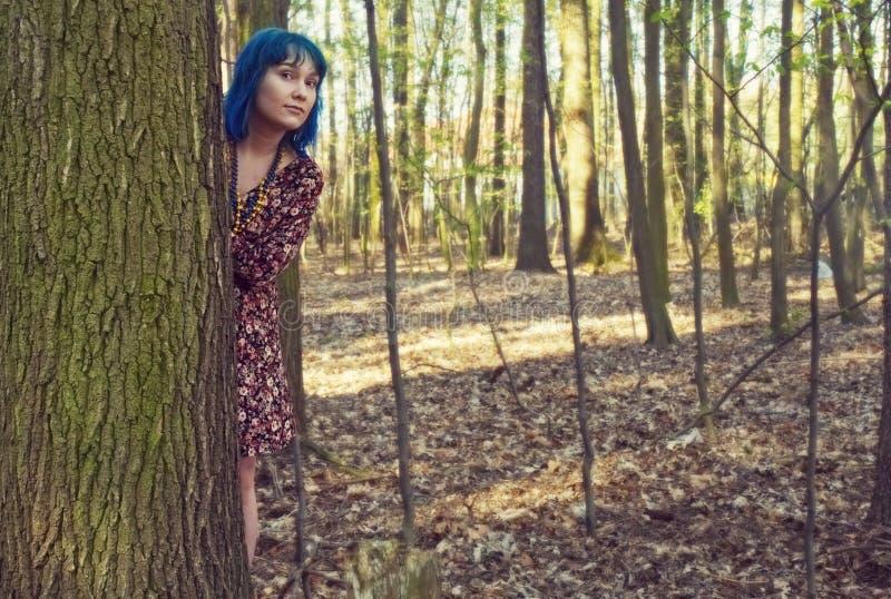 女孩从后面一棵树倾斜在森林里 免版税库存图片