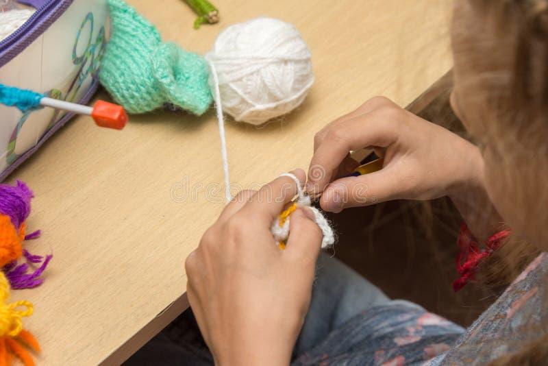 女孩从坐在桌上的螺纹的女裁缝编织 库存图片