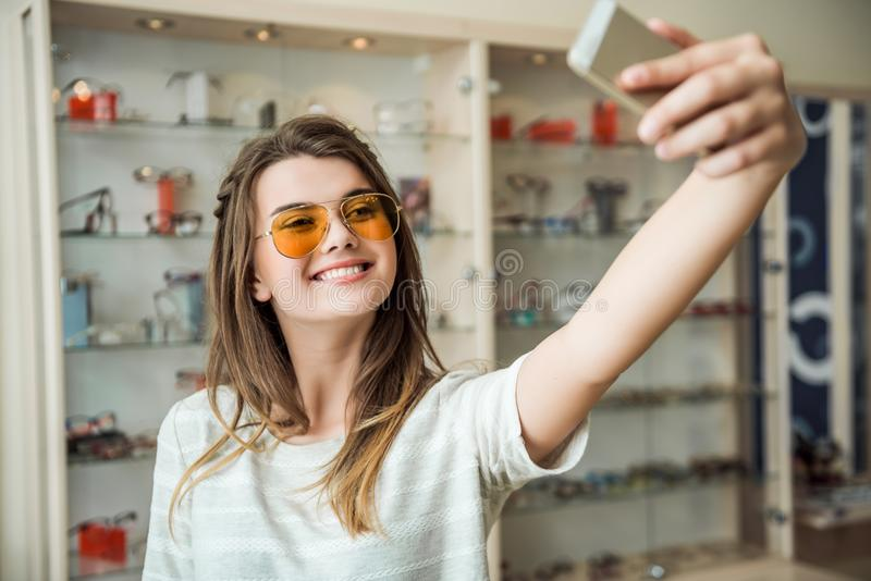 女孩从未居住在家,不用智能手机,尝试在太阳镜的时髦的欧洲浅黑肤色的男人,当采取在电话时的selfie 库存照片