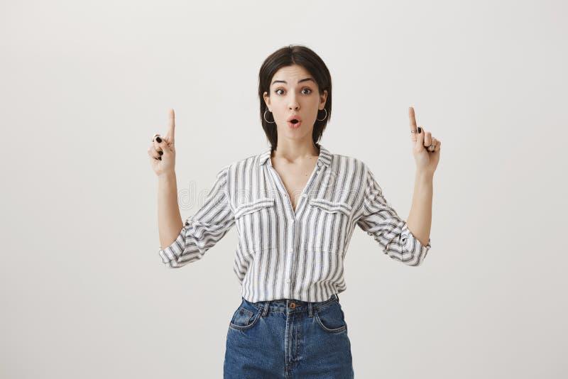 女孩从未看更加惊人的事 时髦的镶边女衬衫和牛仔裤的兴奋的和想知道的白种人妇女 库存图片