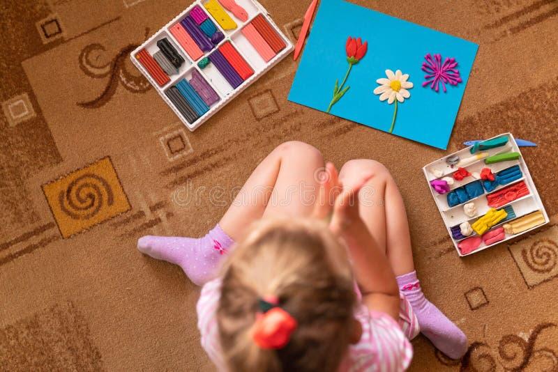 女孩从黏土使用并且雕刻 塑造彩色塑泥和美好的运动技巧的发展 免版税库存照片
