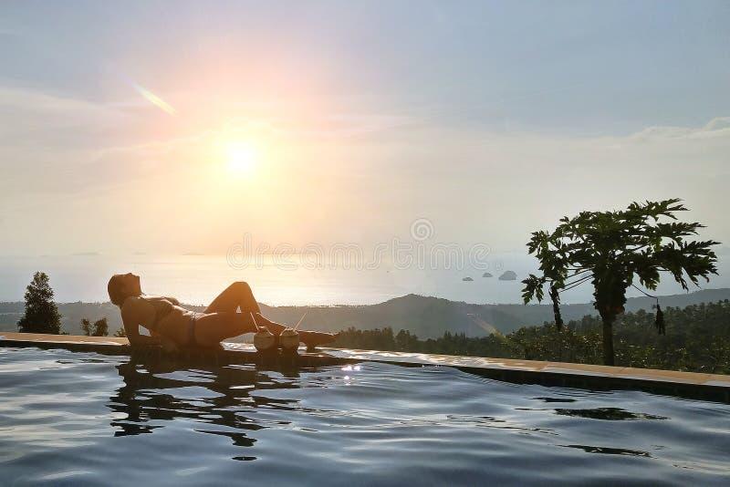 女孩休息在无限水池边缘 俯视热带密林和海滩 在两个椰子附近与 免版税库存照片