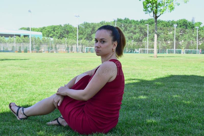 女孩休息的说谎在绿草在公园在夏天 免版税库存图片