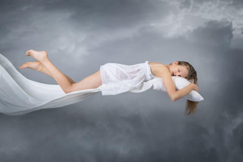 女孩休眠 梦想飞行 在灰色背景的云彩 免版税库存照片