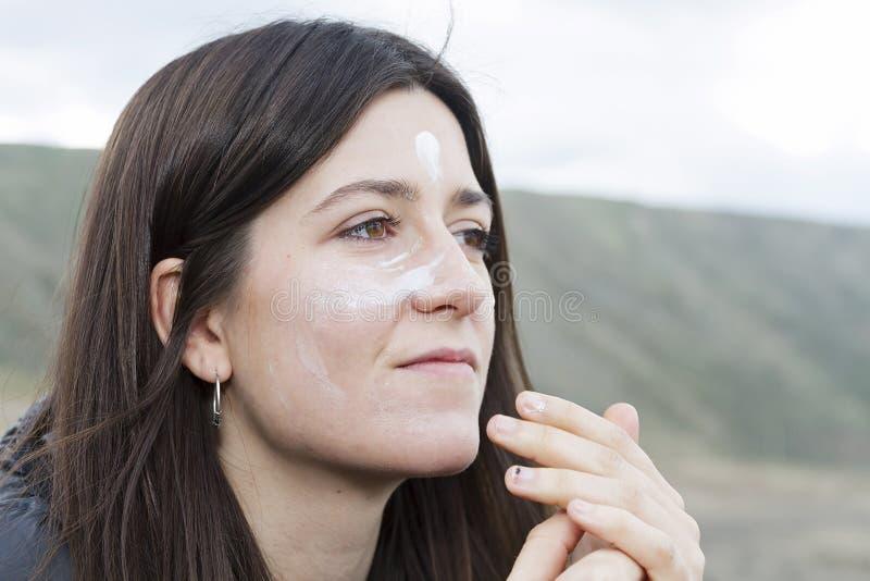 女孩传播的太阳奶油 免版税库存照片
