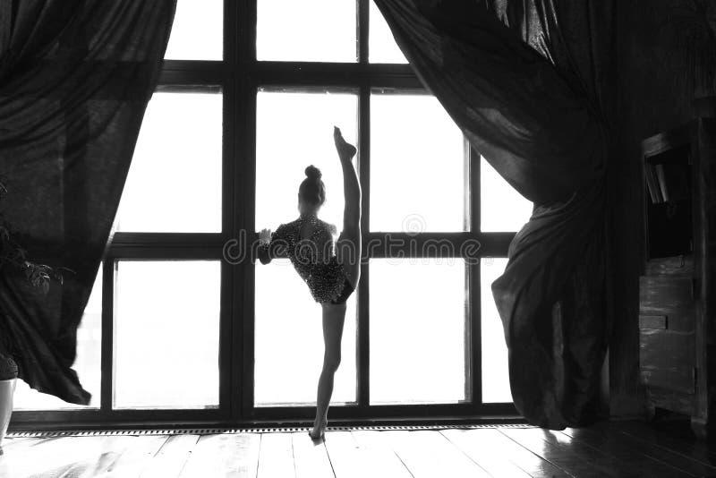 女孩体操运动员被打开在清早在fr醒和做在窗口前面的一锻炼和做一体操锻炼 免版税库存图片