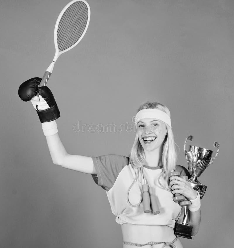 女孩体育辅导员举行金黄觚优胜者或冠军 妇女好在网球跳跃的拳击健身体育 ? 库存图片