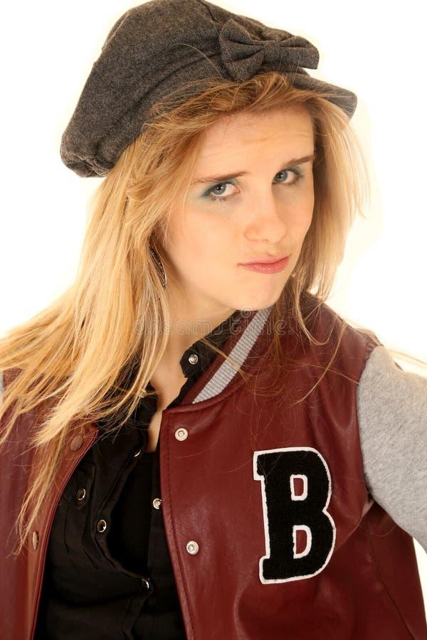 女孩佩带的优秀运动员夹克和帽子有态度的 免版税库存图片