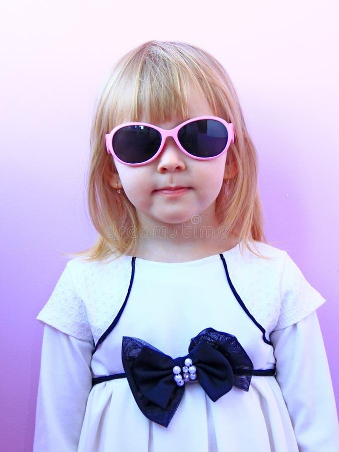 女孩佩带的太阳镜画象在桃红色背景的 戴桃红色太阳镜的少女演播室射击 少许时尚 库存照片