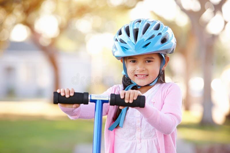 女孩佩带的安全帽骑马滑行车 免版税库存照片