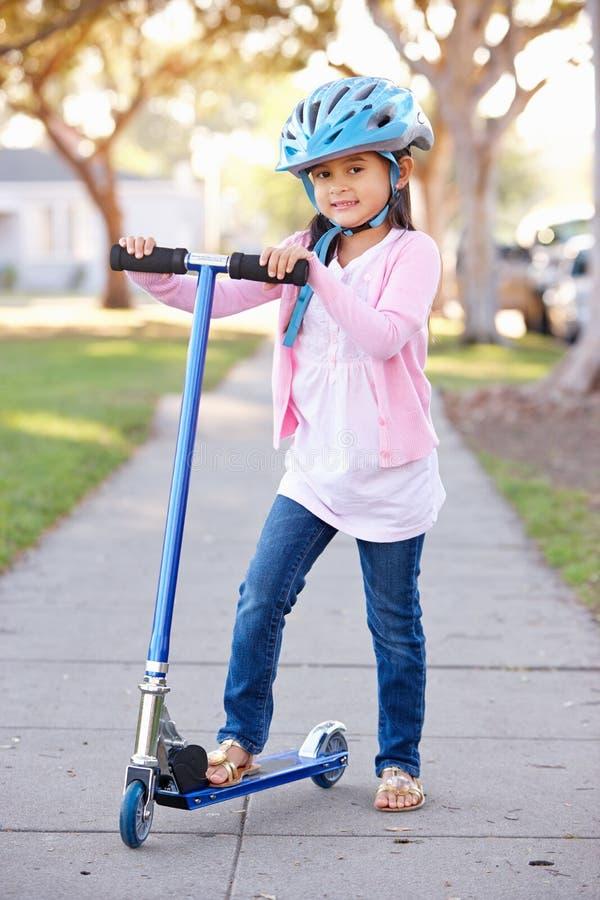 女孩佩带的安全帽骑马滑行车 库存图片