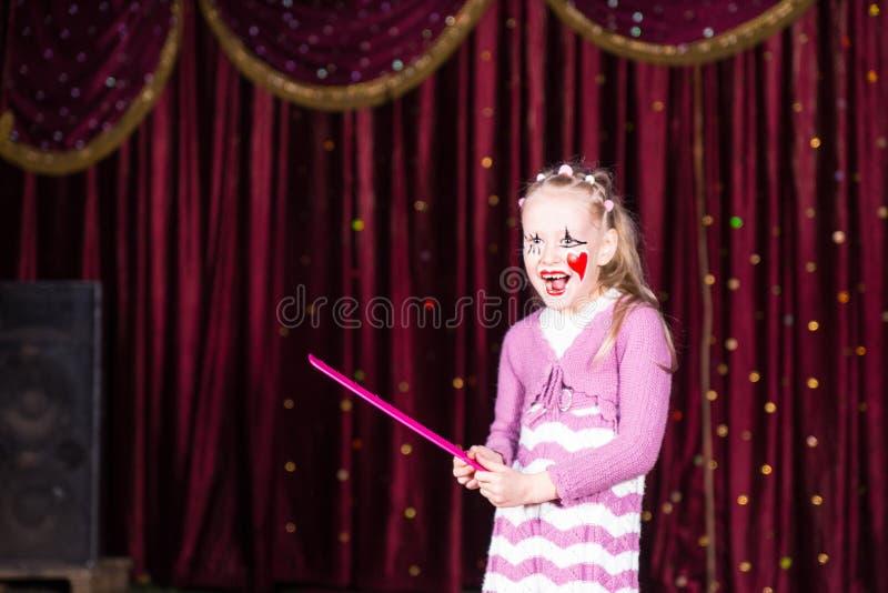 女孩佩带的小丑做停滞大桃红色梳子 库存图片