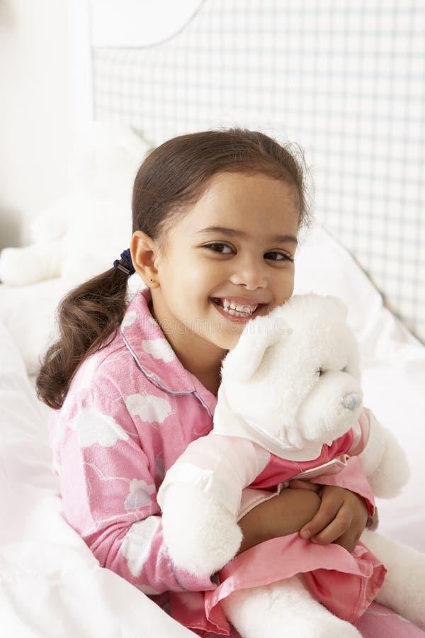 女孩佩带的睡衣在与爱拥抱玩具的床上 库存图片