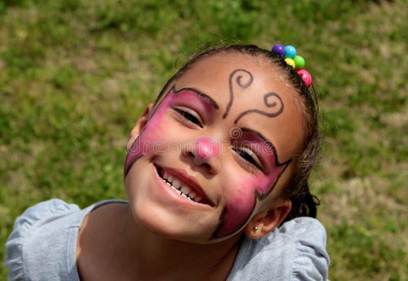 女孩佩带的面孔油漆和明亮微笑 库存照片