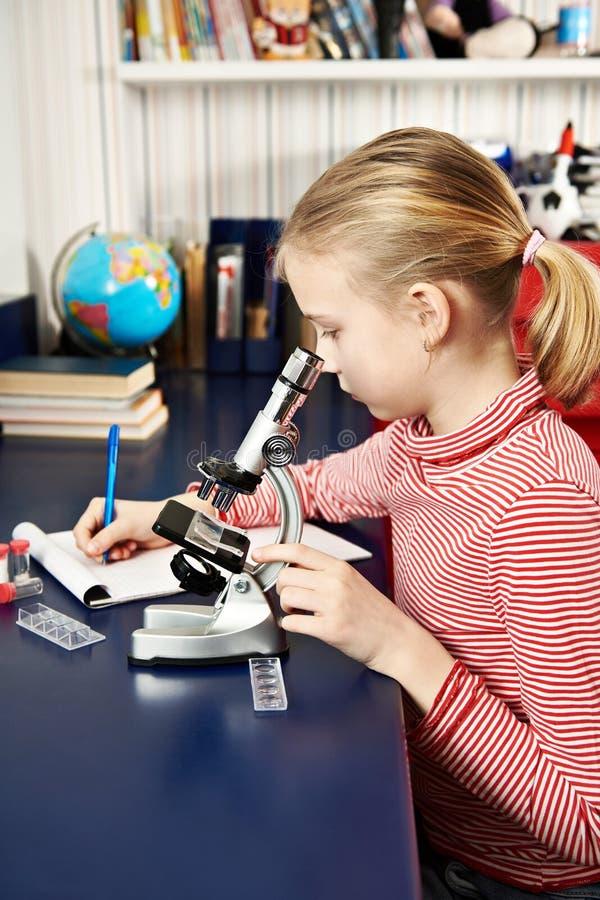 女孩使用一个显微镜并且写结果 免版税库存图片