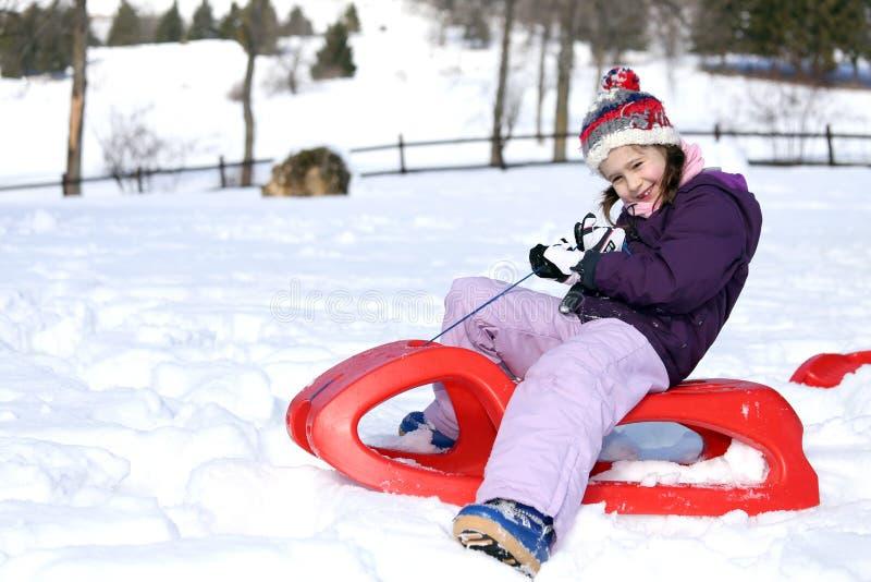 女孩使用与在雪的红色雪撬在山 免版税图库摄影