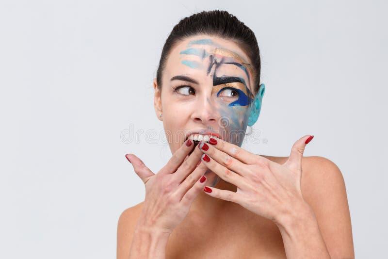 女孩使盖子困窘她的嘴用她的在灰色背景的手 免版税库存图片