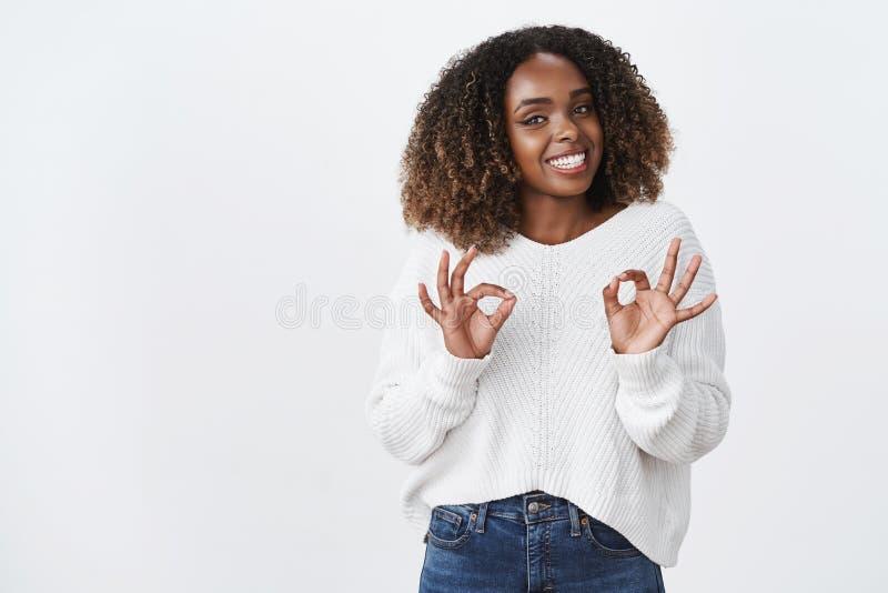 女孩保证顾客一切完成的巨大展示好没有问题ok姿态微笑的友好的宜人的注视照相机同意 库存图片