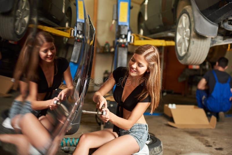 女孩修理有套筒扳手的汽车,在汽车它的反射 免版税库存图片
