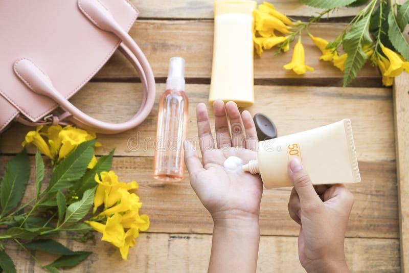 女孩倾斜奶油遮光剂spf50的手为皮肤面孔保护 免版税库存图片