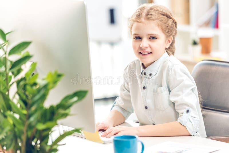 女孩假装是女实业家和与计算机一起使用在办公室 库存图片