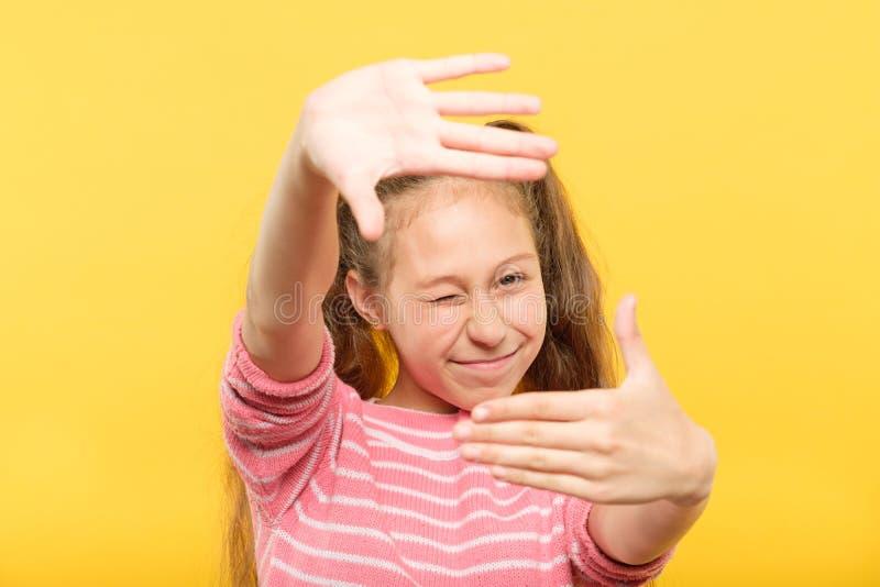 女孩假装采取照片手框架艺术爱好 库存图片