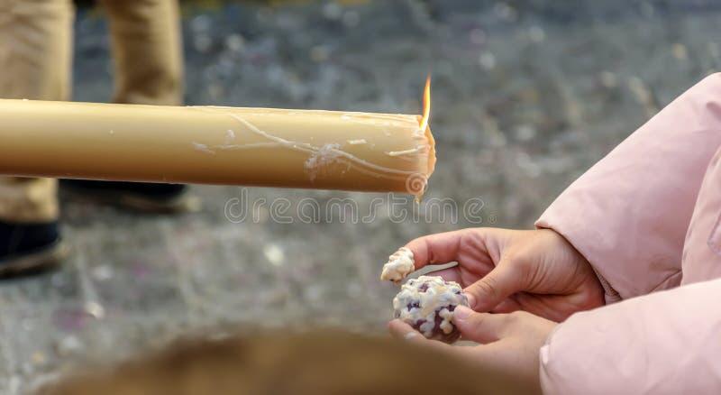 女孩做一个小球蜡,滴下由一个蜡烛在圣周队伍在韦尔瓦省,西班牙 免版税库存照片