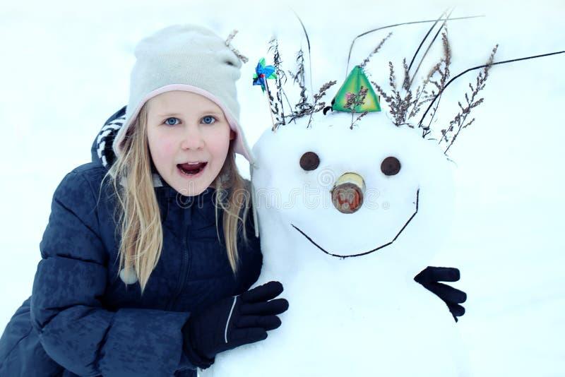 女孩做一个雪人外面在冬时 女孩和雪人微笑着 免版税库存图片